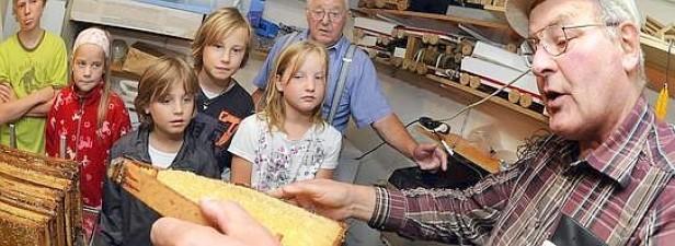 Vor großen und kleinen Zuschauern erklärt Heinz Liesen vom Heimatverein Lembeck, wie Honig geschleudert wird. Foto: André Elschenbroich / WAZ FotoPool