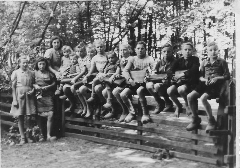 Schüler auf dem Schulweg, sitzen auf Kerkmanns Hoftor