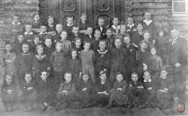 Eine Schulklasse nach der Schuleinweihung 1927. Rechts im Bild: Lehrer Schenuit.