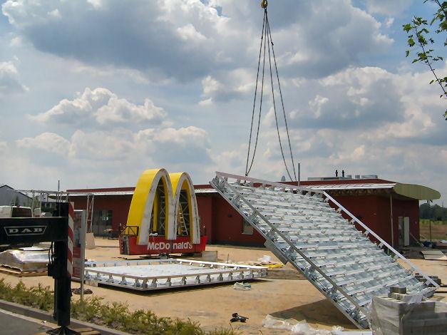 """Die beleuchteten Werbetafeln und das berühmte """"M"""" stehen z.Zt. noch auf  dem Grundstückspflaster, bevor sie spätestens morgen auf die Spitze des Pylons montiert werden."""