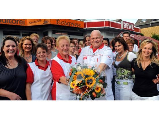 """Neben einem Blumenstrauß bekam Irmgard Thiehoff zum Abschied von Udo Cosanne auch einen Gutschein für ein Verwöhnwochenende in einem Wellnesshotel für sich und Ehemann Günther überreicht, von den Kolleginnen Blumen und das """"Taschengeld"""" dafür. Foto: WAZ, Lutz von Staegmann"""